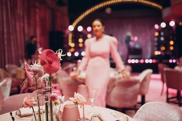 Jantar romântico com decoração rosa em restaurante com mowan desfocado no vestido ao fundo