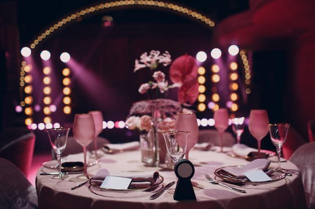 Jantar romântico com decoração rosa em restaurante com palco