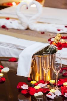 Jantar romântico para os amantes: taças de champanhe, champanhe com gelo em um balde de metal e velas, na parede uma cama decorada pétalas de rosa