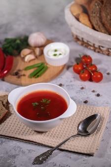 Jantar saboroso e saudável. um prato com sopa de beterraba em cima da mesa, ao lado do tabuleiro, inclui legumes, salsa, endro, cebola verde, alho, pimenta, tomate cereja e pão.