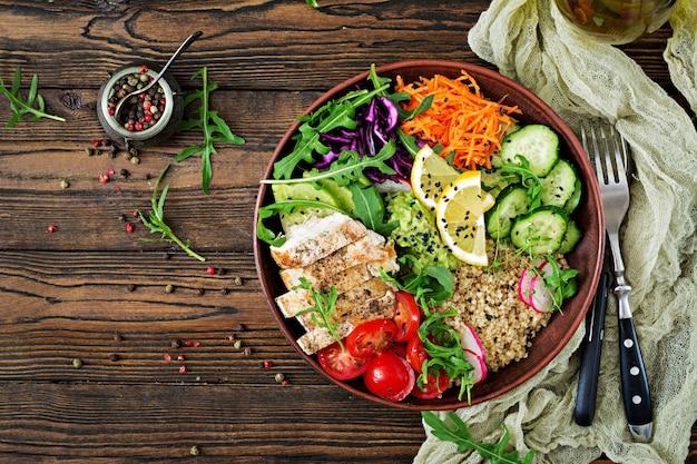 Jantar saudável. almoço de tigela de buda com frango grelhado e quinoa, tomate, guacamole, cenoura, couve roxa, pepino e rúcula na mesa de madeira. postura plana. vista do topo