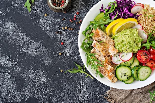 Jantar saudável. almoço na tigela de buda com frango e quinoa grelhado, tomate, guacamole, couve roxa, pepino e rúcula. postura plana. vista do topo