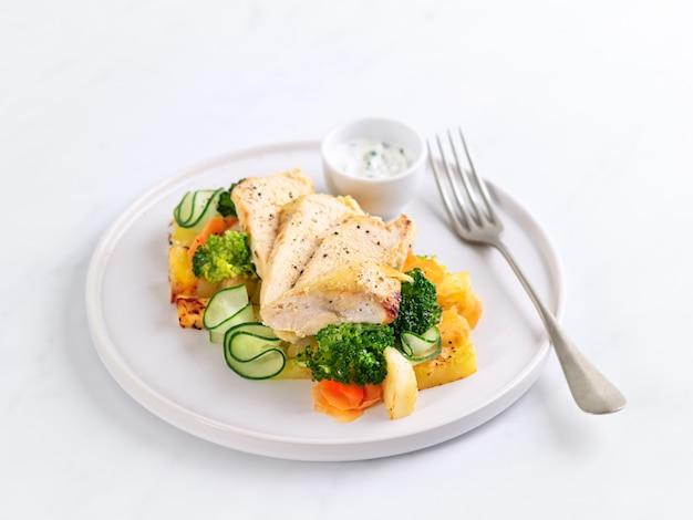 Jantar saudável com molho de frango, batatas grelhadas, pepino, cenoura, brócolis e molho de iogurte na luz de fundo. nutrição apropriada.