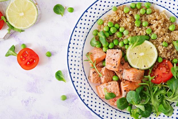 Jantar saudável. fatias de salmão grelhado, quinoa, ervilhas, tomate, limão e folhas de alface. postura plana. vista do topo