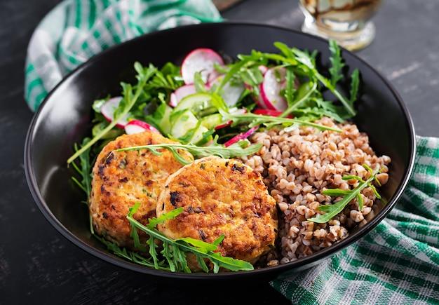 Jantar saudável. merendeira com mingau de trigo sarraceno, costeletas de frango frito e salada de legumes fresca de rúcula, pepino e rabanete.