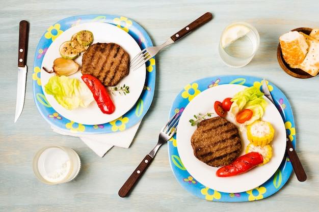 Jantar servido brilhante com bifes e legumes