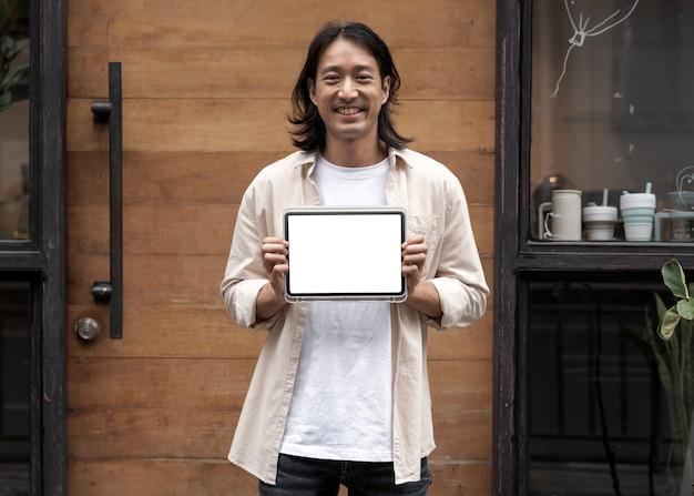 Japonês mostrando a tela de um tablet digital do lado de fora de sua loja