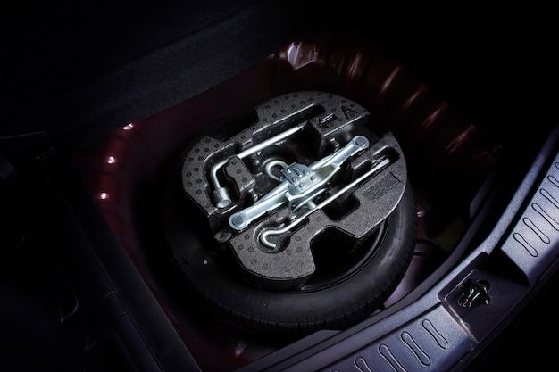 Jaque do carro e jogo de ferramentas em mudança da roda no pneu de reposição do carro.