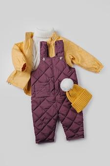 Jaqueta amarela, calça quente e chapéu em fundo branco. conjunto de roupas de bebê para o inverno. roupa de moda infantil.