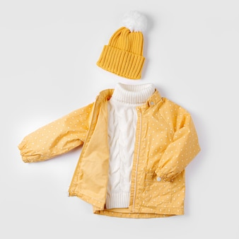 Jaqueta amarela e agasalho quente e chapéu em fundo branco. conjunto de roupas infantis para o outono ou inverno. roupa de moda infantil.
