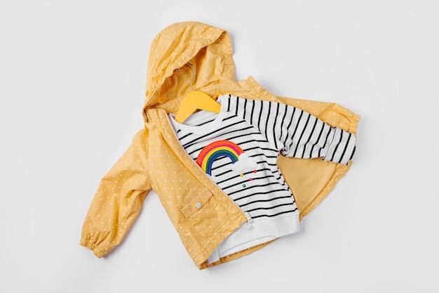 Jaqueta amarela e jumper listrado em fundo branco. conjunto de roupas infantis para o outono. roupa de moda infantil.