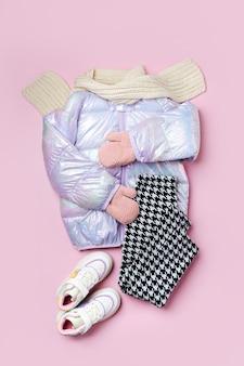 Jaqueta de baiacu quente de crianças com calças e tênis em fundo rosa. casacos infantis elegantes. roupa de moda de inverno
