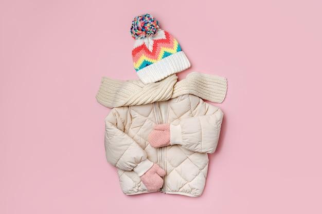 Jaqueta de baiacu quente de crianças com lenço e chapéu em fundo rosa. casacos infantis elegantes. roupa de moda de inverno