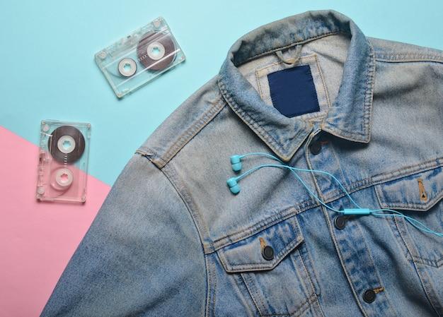 Jaqueta de cassetes de áudio, fones de ouvido e jeans em um fundo cremoso rosa azul. entretenimento e moda dos anos 80.