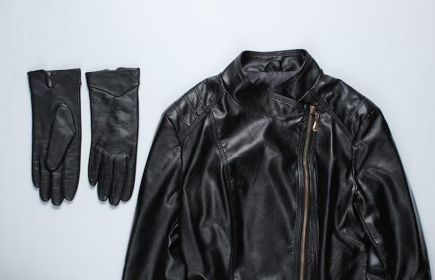 Jaqueta de couro, luvas na superfície cinza.