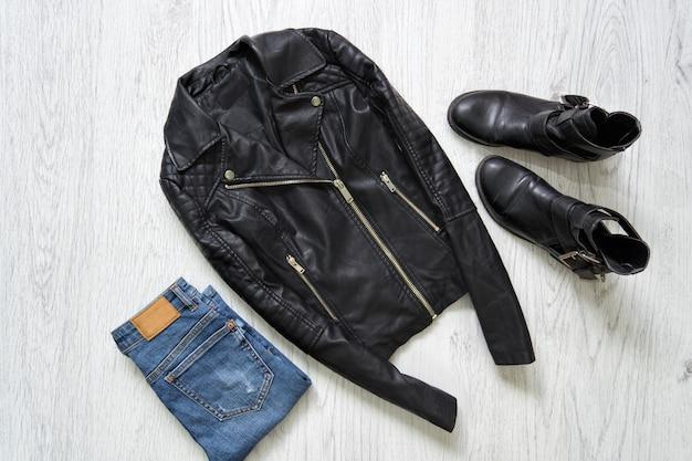Jaqueta de couro preta, jeans e botas.