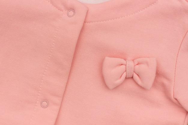 Jaqueta elegante rosa de parte menina com close-up de proa, textura de fundo
