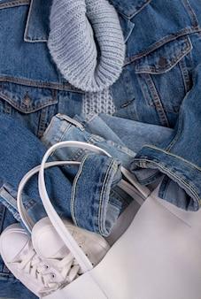 Jaqueta jeans azul, tênis de couro branco, bolsa branca em uma superfície branca