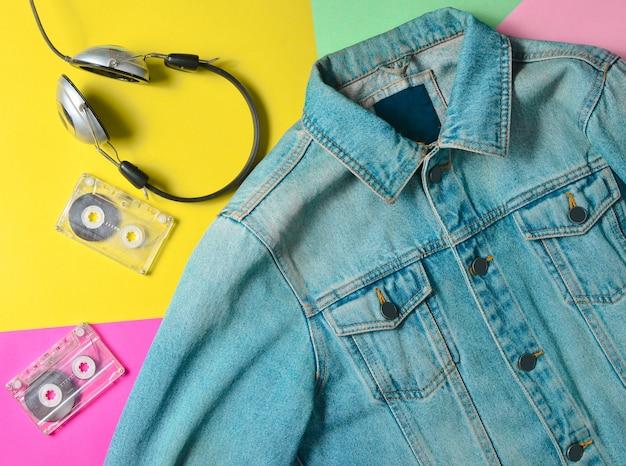 Jaqueta jeans, cassetes de áudio e fones de ouvido são revestidos em uma superfície de néon multicolorida. moda dos anos 80. olhar na moda. postura plana.
