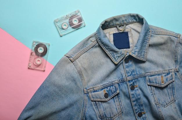 Jaqueta jeans e cassetes de áudio em um fundo cremoso rosa azul. entretenimento e moda dos anos 80.