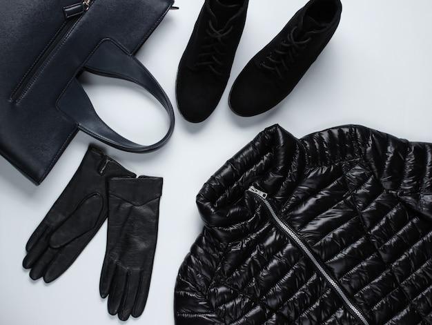 Jaqueta, luvas, bolsa, botas em uma superfície cinza.