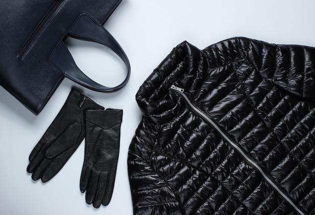 Jaqueta, luvas, bolsa em uma superfície cinza.
