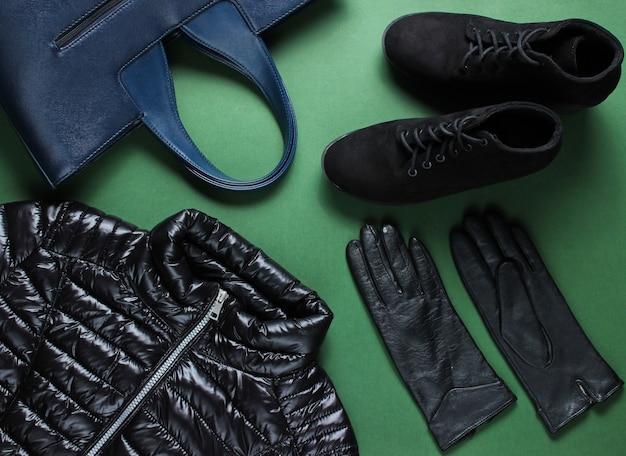Jaqueta, luvas, botas, bolsa na superfície verde.