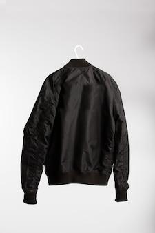 Jaqueta preta em cabide de pano com parede branca