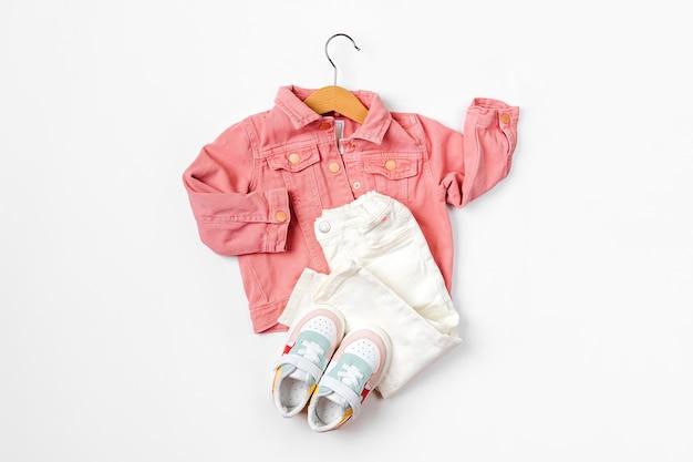 Jaqueta rosa em cabide e calça com tênis. conjunto de roupas de bebê e acessórios para a primavera, outono ou verão em fundo branco. roupa de moda infantil. camada plana, vista superior
