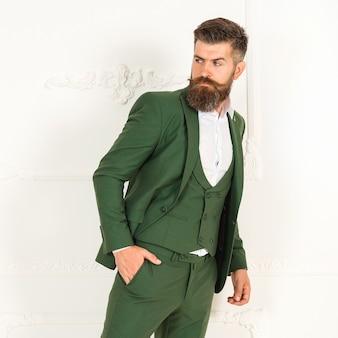 Jaqueta verde masculina bonita com camisa em homem barbudo sexy brutal. retrato da moda da pessoa séria com barba em elegante terno verde na sala branca com interior clássico. modelo de moda jovem