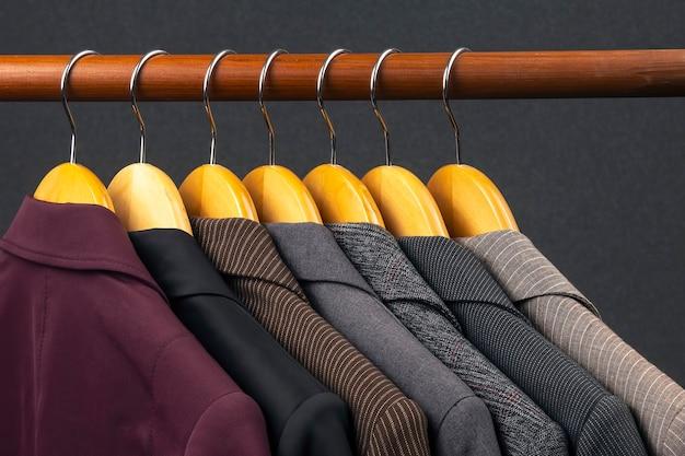 Jaquetas e camisas clássicas de escritório para mulheres diferentes penduradas em um cabide para guardar roupas