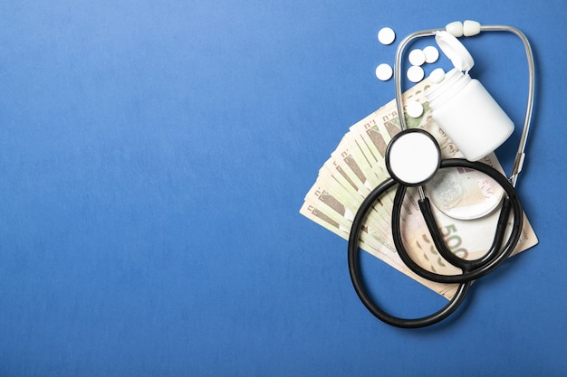 Jar com comprimidos e um estetoscópio sobre um fundo azul. o conceito de medicina e saúde. preços mais altos de medicamentos. política e saúde
