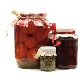 Jar com conservas. geléia de morango caseira, tomate em conserva e alcaparras isoladas no fundo branco