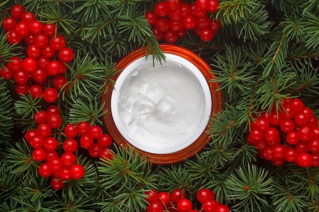 Jar com creme hidratante para o rosto no fundo de ramos de abeto, coníferas e bagas de viburnum.
