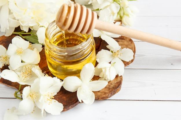 Jar e uma colher com mel em um carrinho de madeira com flores de jasmim