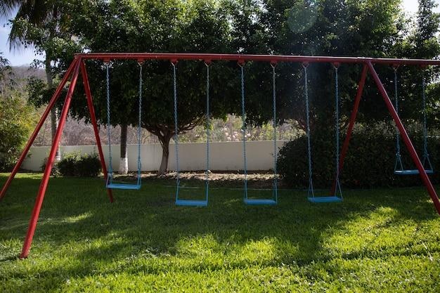 Jardim cercado por vegetação e balanços azuis e vermelhos sob a luz do sol em huatulco, no méxico