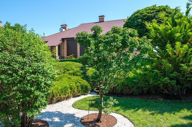 Jardim com arbustos e árvores bem aparados em frente à villa de estilo europeu. projeto paisagístico. foto de alta qualidade