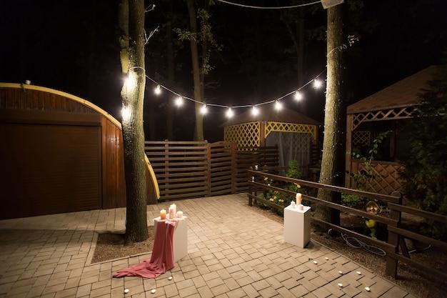 Jardim com gazebo de madeira com luzes, velas à noite em um casamento