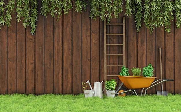 Jardim com uma cerca de madeira velha e ferramentas para jardinagem