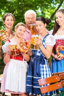 Jardim da cerveja - amigos bebendo na baviera pub