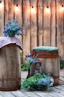 Jardim de verão com palco de madeira e guirlanda de luzes para festas ou casamento ao ar livre.
