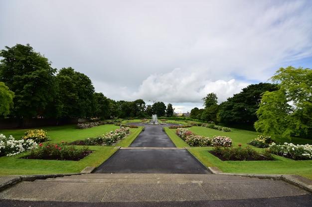 Jardim do castelo de kilkenny, rodeado por vegetação sob um céu nublado na irlanda
