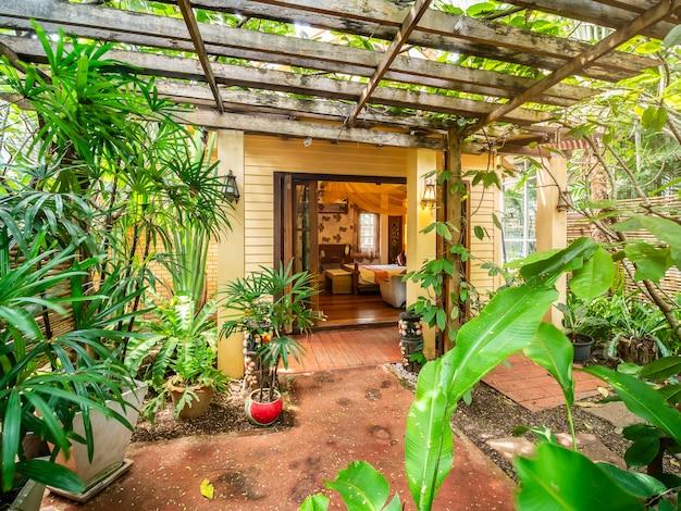 Jardim na frente do quarto de luxo com cama com decoração vintage, estilo de bali.