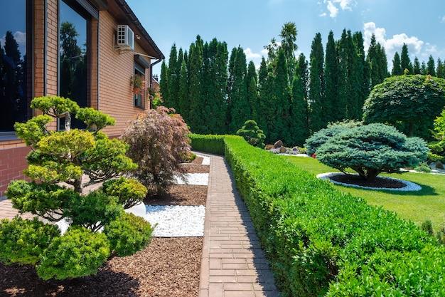 Jardim no quintal com arbustos de bonsai bem aparados e arbustos ao lado da villa