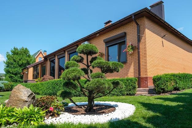 Jardim nos fundos com arbustos de bonsai bem aparados e arbustos na frente da villa