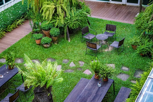 Jardim público com cadeira de madeira e mesa decorada com pequena árvore ao redor.