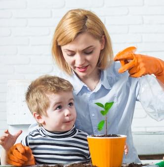 Jardinagem e plantio, mãe com filho pulverizando flores, cuidando das plantas.