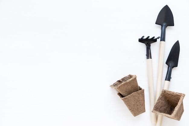 Jardinagem em casa. cultivo de alimentos no peitoril da janela. ferramentas, vasos de turfa para mudas. copyspace para texto, vista superior. flatlay em fundo branco de madeira.