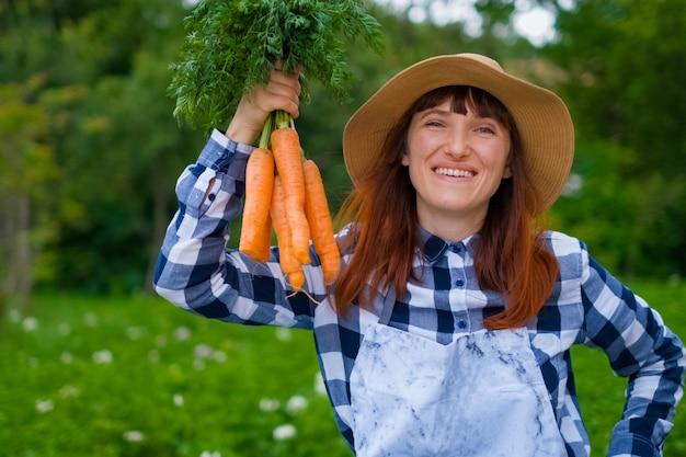 Jardinagem - mulher jovem e bonita com cenouras orgânicas em uma horta. luz de fundo