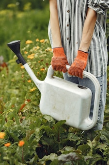 Jardinagem no verão. mulher regando flores com um regador. menina com um chapéu.